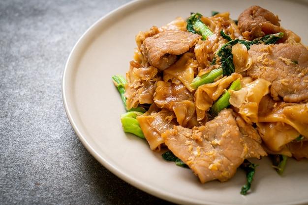 Spaghetti di riso saltati in padella con salsa di soia nera e maiale e cavolo nero - stile alimentare asiatico