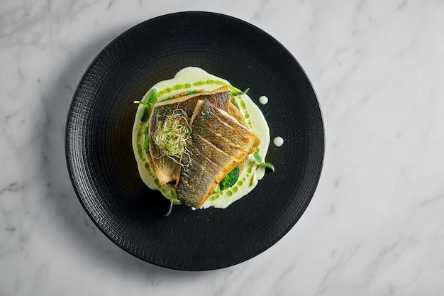 Filetto di branzino saltato in padella con quinoa e broccoli guarnito con salsa cremosa, servito in un piatto nero su marmo