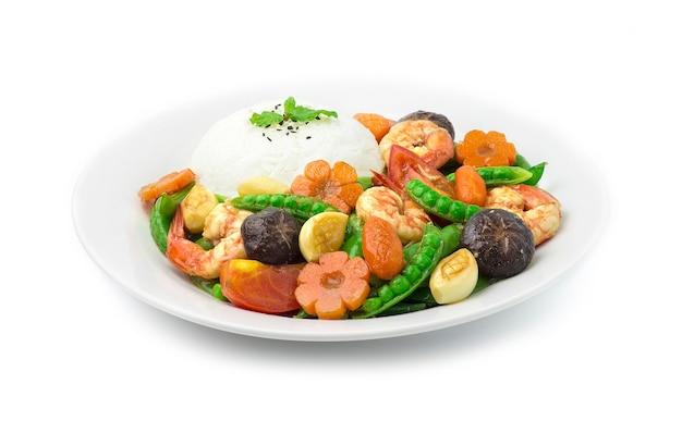 Piselli saltati in padella con gamberi gamberi carote intagliate fiore e forma di mais e aglio servito con riso