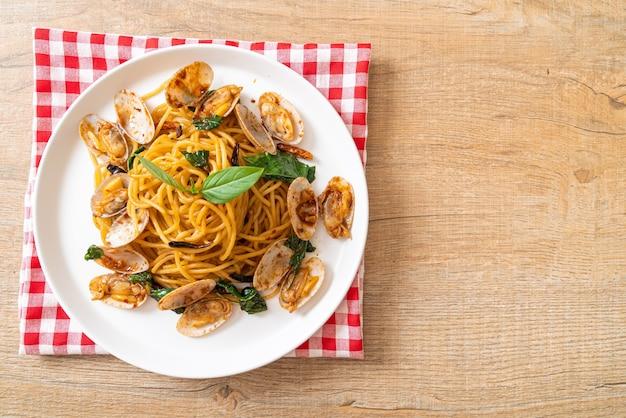 Spaghetti saltati in padella con vongole e aglio e peperoncino. stile di cibo fusion