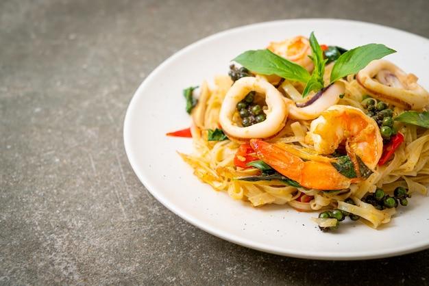 Tagliatelle piccanti saltate in padella con frutti di mare (pad cha talay) - stile di cibo tailandese