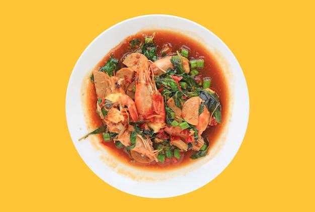 Gamberi saltati in padella e salsiccia di maiale con foglia di basilico sul piatto in ceramica cerchio isolato su sfondo giallo.