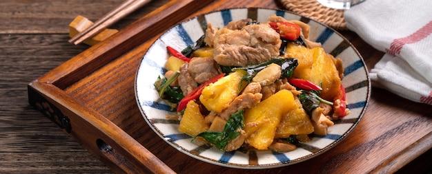 Pollo tre tazze taiwanese saltato in padella con ananas. cibo delizioso fatto in casa a taiwan sulla superficie del tavolo in legno scuro.