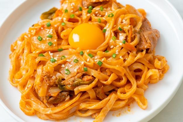 Noodles udon saltati in padella con kimchi e maiale - stile di cucina coreana