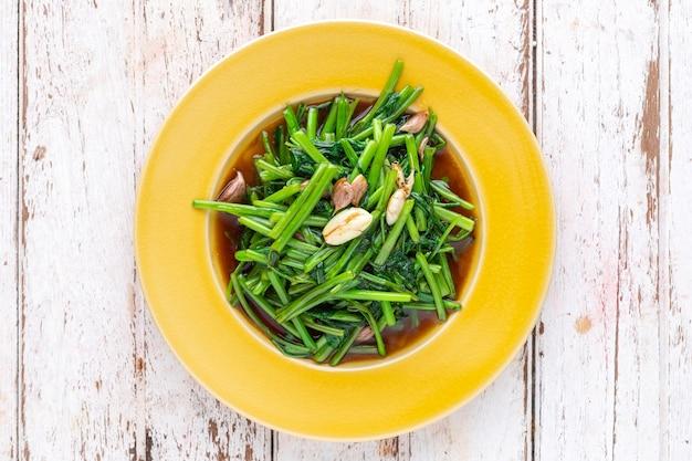Mescolare gli spinaci d'acqua fritti con aglio in piatto di ceramica gialla su sfondo bianco di legno vecchio, vista dall'alto, fotografia di cibo leggera e ariosa, gloria mattutina