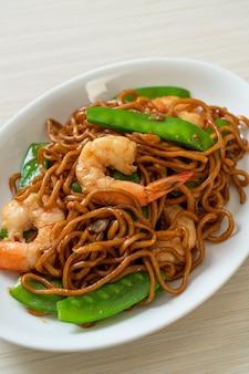 Spaghetti di yakisoba saltati in padella con piselli e gamberetti - stile di cibo asiatico
