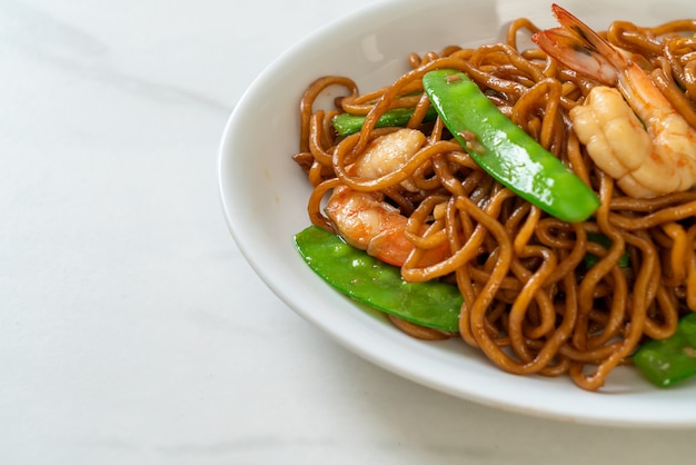 Spaghetti di yakisoba saltati in padella con piselli e gamberi. stile di cibo asiatico