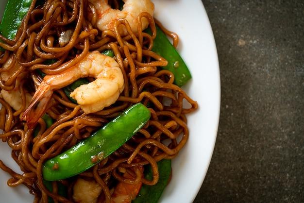 Noodles di yakisoba saltati in padella con piselli e gamberi - cucina asiatica