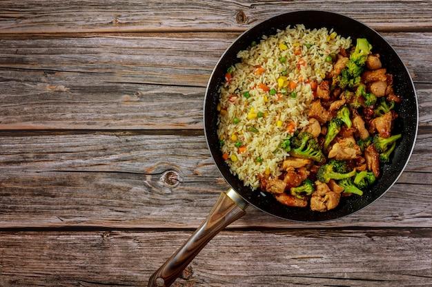 Pollo saltato in padella con broccoli in salsa agrodolce e riso. pasto asiatico.