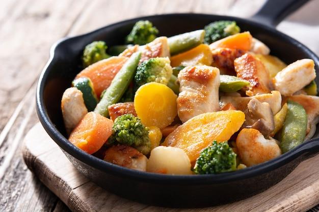 Mescolare il pollo fritto con le verdure sulla padella di ferro sul tavolo di legno
