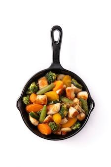 Saltare in padella il pollo con le verdure su una padella di ferro