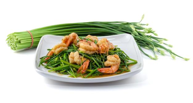 Erba cipollina cinese di fioritura in padella con i gamberetti in piatto isolato su bianco