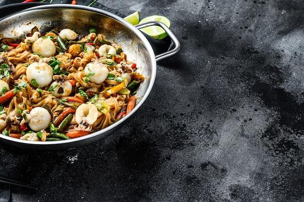 Soffriggere i noodles con seppie e verdure in una padella wok