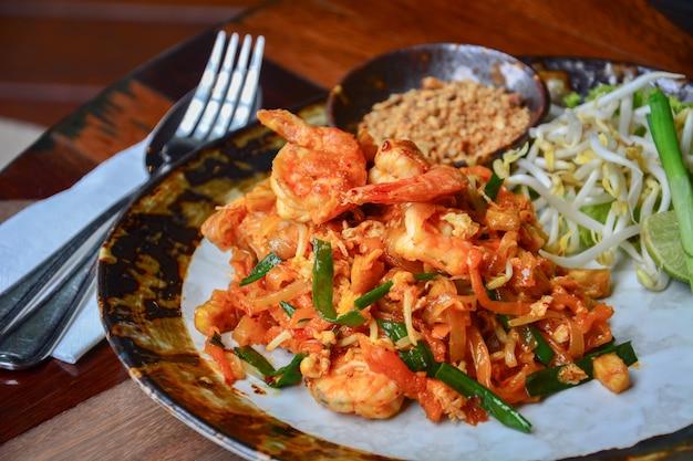 Saltare in padella gli spaghetti di riso con gamberi e verdure o pad thai su sfondo di tavolo in legno