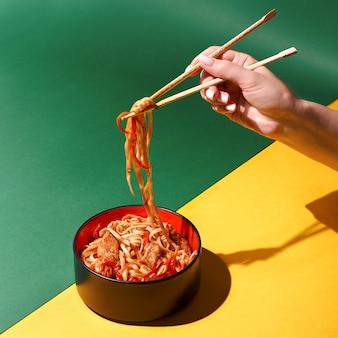 Soffriggere le tagliatelle di soba con carne di manzo e verdure nel wok su sfondo scuro, tagliatelle di udon asiatico con manzo wok in ciotola nera su sfondo di ardesia. copia spazio con ombre dure