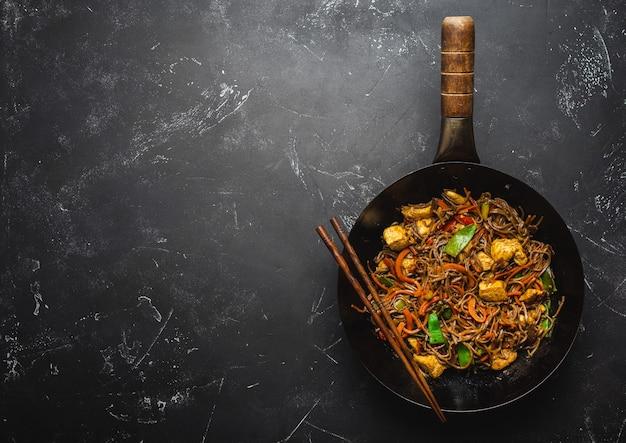 Soffriggere le tagliatelle di soba con pollo, verdure in una vecchia padella wok rustica, bacchette su sfondo di pietra nera, primo piano, vista dall'alto. pasto tradizionale asiatico/thai, spazio per il testo