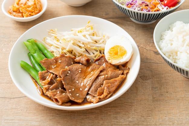 Maiale teriyaki saltato in padella con semi di sesamo, germogli di fagioli mung, uova sode e set di riso - stile alimentare giapponese