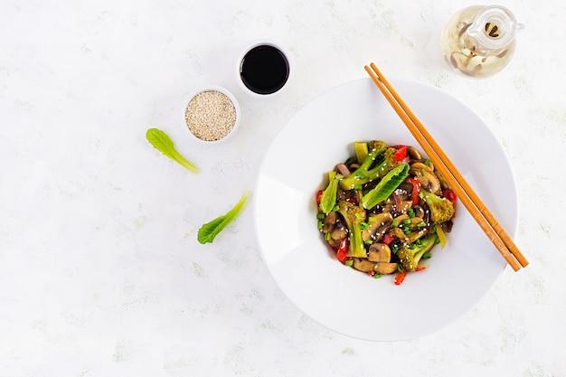 Soffriggere le verdure con funghi, paprika, cipolle rosse e broccoli. cibo salutare. cucina asiatica. vista dall'alto, in alto