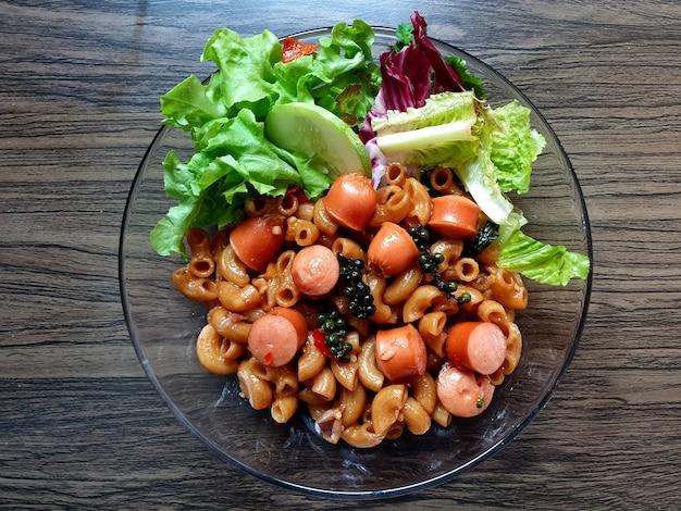 Pasta saltata in padella con salsiccia e verdure su tavola di legno
