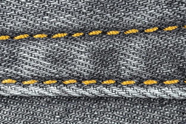 Cucitura sul primo piano del fondo di struttura del tessuto del jeans del denim nero con alta risoluzione