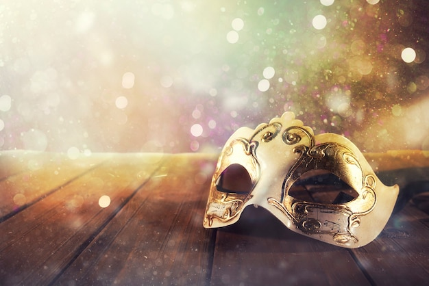 Ancora la vita di una maschera di carnevale vintage su un pavimento di legno