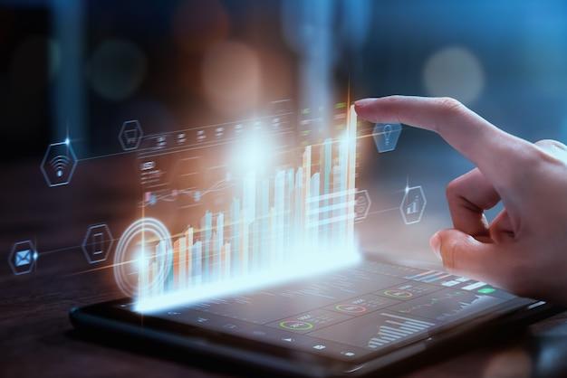 Concetto del mercato di borsa, commerciante della mano della donna di affari premere la compressa digitale con l'analisi dei grafici
