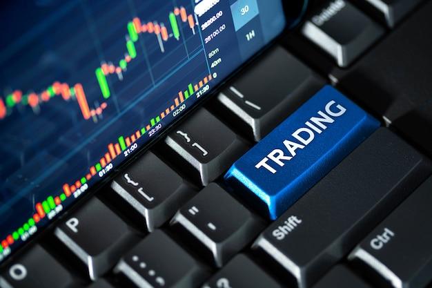 Schermata del grafico del mercato azionario sulla tastiera del computer e sul pulsante blu di trading, concetto di investimento online