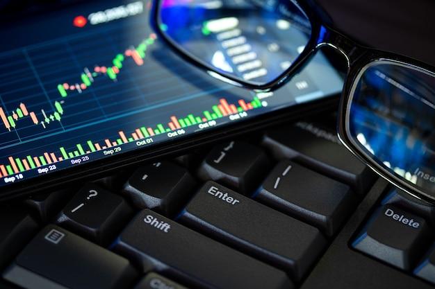 Schermo del grafico del mercato azionario sulla tastiera del computer e degli occhiali, concetto di investimento online