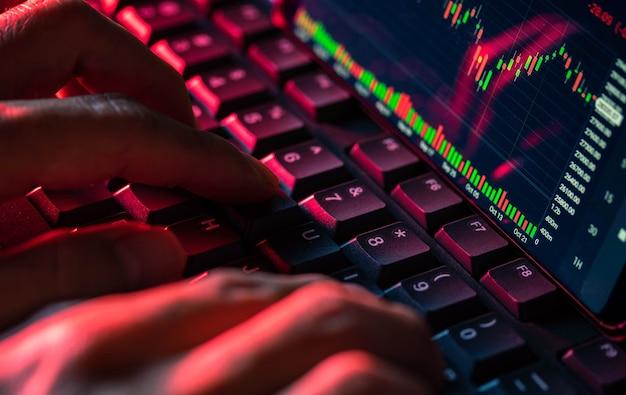 Schermo del grafico del mercato azionario sulla tastiera del computer e le dita toccano, concetto di investimento online