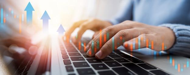 Mercato azionario e concetto di commercio di criptovaluta finanziaria, mano ravvicinata di una donna che lavora freelance, commercia e digita su laptop con grafico a casa