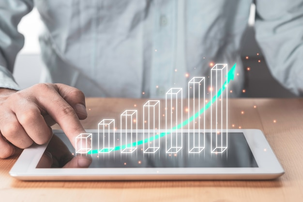 Investimenti in borsa e crescita dei profitti aziendali, uomo d'affari che punta a tablet con grafico e grafico in aumento virtuale.