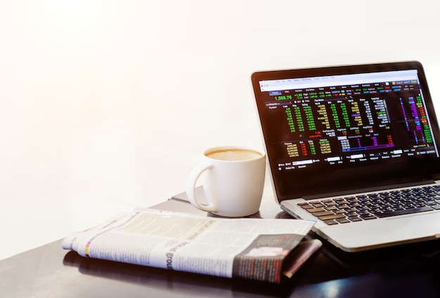 Mercato azionario in notebook con giornale e tazza di caffè