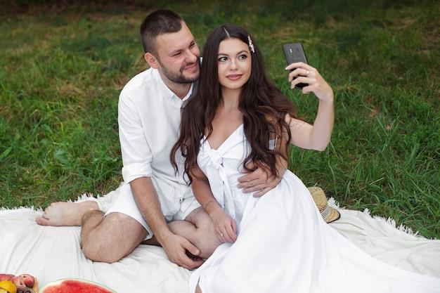 Foto di stock di una bella coppia in abiti bianchi seduti sulla coperta da picnic. bella ragazza con lunghi capelli castani in abito bianco che tiene il telefono cellulare e prendendo selfie.