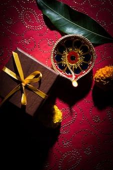 Foto di stock di bella diwali diya con doni e fiori, su sfondo decorativo, illuminazione lunatica e messa a fuoco selettiva
