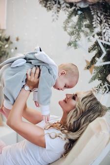 Foto di stock di allegra madre che gioca con il bambino figlio in costume da coniglio rilassante sull'altalena. natale.