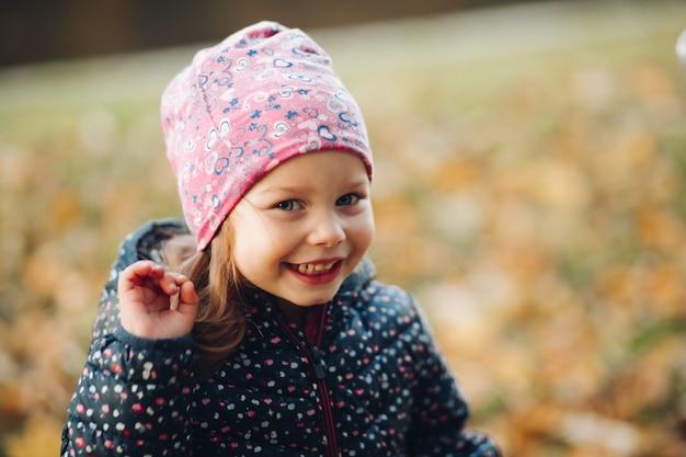 Foto di stock di una ragazza carina che indossa un cappello stampato rosa e una giacca invernale stampata scura che sorride e agita la mano.