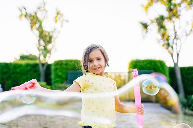 Foto di stock di una ragazza che gioca in strada con bolle di sapone al tramonto una giornata di sole