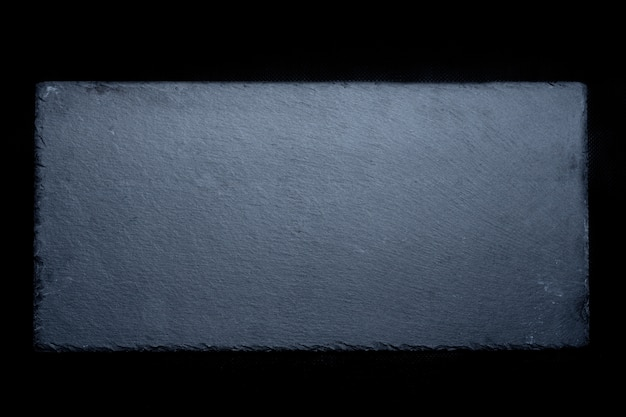 Foto di riserva dell'ardesia grigia naturale su fondo nero.
