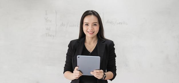 Foto di stock ritratto di un'insegnante donna asiatica allegra fiduciosa in un'uniforme nera con un tablet digitale e un laptop per insegnare la lingua moderna in classe