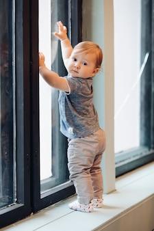 Stock photo ritratto in piena lunghezza di carino piccolo neonato in piedi vicino alla finestra. sta guardando indietro alla telecamera. alzando la mano sulla finestra.