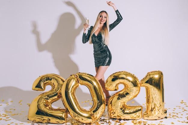 Foto di stock di splendida modella bionda in abito da cocktail in posa con braccio alzato e bevanda alcolica in vetro in posa davanti a cifre dorate gonfiabili e coriandoli sparsi.