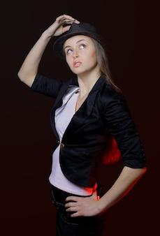 Fotografia stock: donna con le labbra aperte in cappello nero su fondo scuro