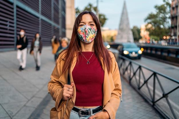 Foto di stock di una giovane donna caucasica guardando la fotocamera. indossa una maschera facciale a causa di covid19
