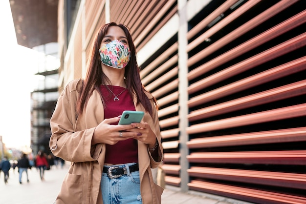 Foto di stock di una giovane donna caucasica utilizzando il suo smartphone in strada. indossa una maschera facciale a causa di covid19.