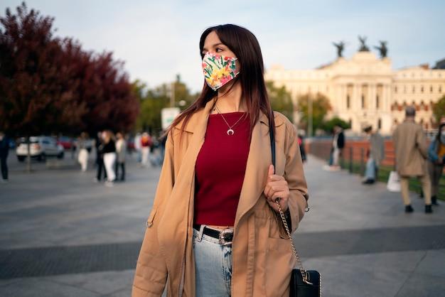 Foto di stock di una giovane donna caucasica che cammina in strada. indossa una maschera facciale a causa di covid19
