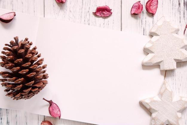 Fotografia stock pigna del mestiere dei petali del taccuino in bianco della tavola di legno verniciata bianca d'annata di disposizione piana