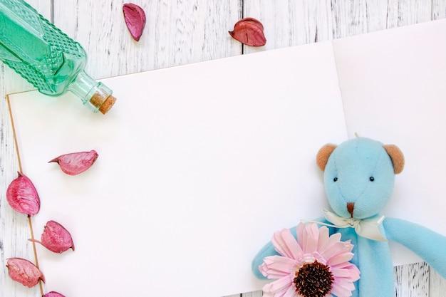Fotografia stock i petali porpora del fiore della tavola di legno verniciata bianca d'annata di disposizione piana portano la bottiglia di vetro verde della bambola