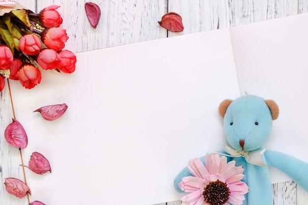 Fotografia stock bambola dell'orso dei petali viola del fiore della tavola di legno verniciata bianca d'annata di disposizione piana è aumentato