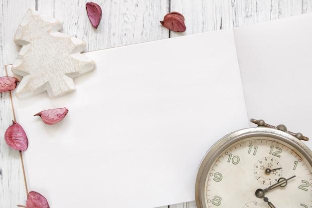 Fotografia stock mestiere d'annata dell'albero di natale della sveglia dei petali viola del fiore della tavola di legno verniciata bianca d'annata di disposizione piana
