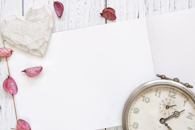 Fotografia stock mestiere d'annata del cuore della sveglia dei petali viola del fiore della tavola di legno verniciata bianca d'annata di disposizione piana